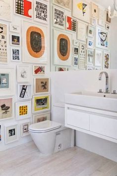 Modern gallery wall layout - floor to ceiling colorful prints in white frames cover the wall in a bathroom. Very inspired! - Art Wall Ideas & Decor