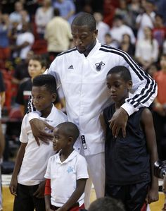 Miami Heat's Dwyane Wade stands with his sons Zaire, right, and Zion, center, and his nephew Dahveon Morris, left, during the playing of the national anthem before an NBA basketball game against the Washington Wizards in Miami, Saturday, Dec 15, 2012. (AP Photo/Alan Diaz)