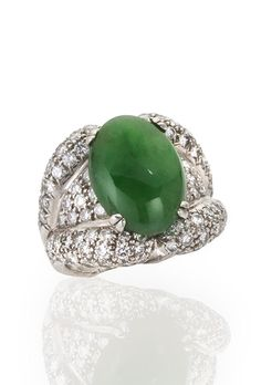 A jadeite jade and diamond ring  centering an oval-shaped cabochon jade measuring approximately 17.20 x 12.25 x 6.60mm., within broad tapered shoulders of pavé-set round brilliant-cut diamonds and completed by a fluted mount