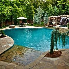 Curvlinear pool with natural boulder waterfall - i want this to be my backyard!