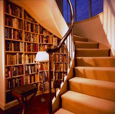 らせん階段のねじれに合わせて作られたびっしりと本が並ぶ本棚。