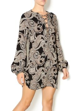Paisley dress features a lace up front, bell sleeves with button cuff and tunic-style hem.