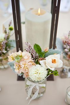 Rustic lantern surrounded by mason jar arrangements tied with lace ribbon. | by Gavita Flora