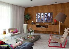Sala de estar   O painel de imbuia apoia a TV e o móvel suspenso. Vasos da Atrium. Poltronas, luminária de piso, mesas de centro e lateral, da Micasa. Almofadas da Empório Beraldin. Cortina de linho da 3 Irmãs Cortinas (Foto: Luis Gomes)