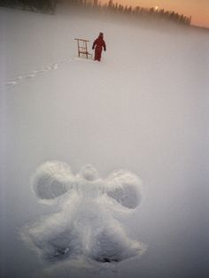 A Figure of an Angel in the Snow and a Child with a Kick Sledge in Background Photographic Print at Art.com