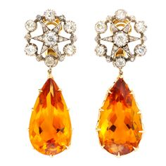 These earrings are from around 1880. They are 18k gold, with the diamonds in silver settings, as was the custom of the time. The drops are citrine. In total, they are about 2.25'' long.