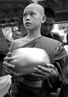 Young buddhist monk collecting donations.    http://www.hello-thailand.net/