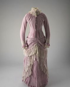 1883 Dress Culture: English Medium: wool Dating from about 1885, this full length dress is made from fine wool, is pink/musk in colour and is elaborately trimmed with cream lace. The tight-fitting bodice is lined and boned, with a high standing collar trimmed with lace that is identical to that used on the cuffs of the full length sleeves. The bodice has lost its original fastening; copper ball buttons featuring an anchor motif have been added at a later stage.