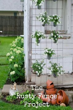 Beautiful garden touches and decor using found items like this rusty fence ~ I love the floating look to the plants