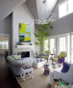Bright green upholstered chairs and purple accessories pop against the pale grey ceiling and white walls of this California wine country living room designed by Stephen Shubel.    Try it at home: Pick up an array of purple and green flowering plants at the nursery (or grocery store) and plant them in simple grey ceramic pots.    - HouseBeautiful.com