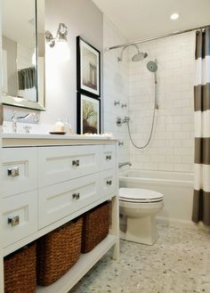 Fun, bright white and gray bathroom with West Elm Stripe Shower Curtain in Feather Gray. White subway tiled bath, black and white photography and nickel sconces. Pale gray walls and white countertop and vanity with basket storage. Mini hexagonal marble mosaic floor and mirror framed mirror.