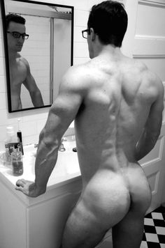 Hunky buffed nerd looking into a mirror