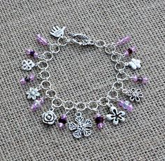 "Flowers Charm Chain Bracelet Pinks Purples Crystals $14.00  If you have a love for flowers, you will love this charm bracelet.  There are 7 silver (tibetan and plated) flower charms and one ""Hand made"" charm with 4mm and 6mm faceted pink and purple crystal beads and a tibetan silver flower toggle clasp attached to silver plated jump rings.  It can be adju..."