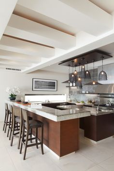 """Valencich added Solistone to the back wall to create a focal point in the kitchen and removed the upper cabinets to open up the space. She then had the remaining cabinets refinished but kept the counters. The extra-thick poured-concrete bar """"adds a nice weight to the kitchen, which is quite large."""" Eight pendant lamps from HD Buttercup hang from a custom-made wood ceiling panel. The black-and-white landscape is by photographer August Dering."""