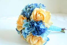 A vibrant bouquet hand-tied with real touch roses and real touch hydrangeas in champagne/ golden yellow/ light peach and blue. A grooms' boutonniere is also included.