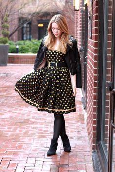 Total look en negro, vestido negro con vuelo y topitos de color amarillo, biker de cuero negra con medias y botines negros.