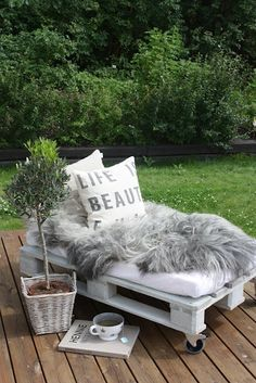 pallet outdoor bench with an up-cycled crib mattress.