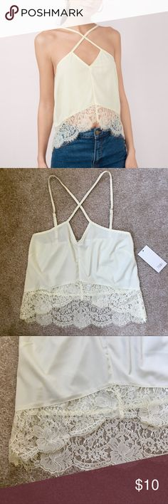 NWT Tobi Cream Criss Cross Lace Tank Top NWT criss cross front tank with hi-low lace hem. Size XS. Color is described as cream, but has a light yellow tint to it. In perfect condition and has adjustable straps. Tobi Tops Tank Tops