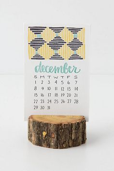 Wood Stump Calendar #anthropologie - The wood matches well with little sketchy graphics. Cute, minimal and charming. The small stump beats the typical clear plastic props. | find this at anthropologie.com | #greendorm