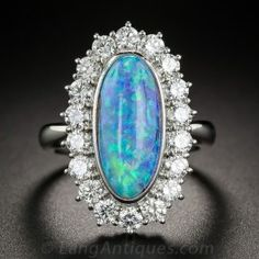 Just shy of an inch long, this strikingly lovely estate dinner ring, hand-fabricated in platinum, highlights an absolutely stunning, elongated oval Australian black opal, weighing 4.18 carats, aglow with an enchanting array of confetti-like colors: predominantly electric turquoise blue, purple and green interposed with occasional flashes of orange. The fabulous gemstone is enshrined in a sparkling white halo of round brilliant-cut diamonds totaling 1.35 carats.  Size 5 3/4.