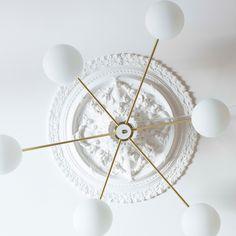 Lampen har et moderne og grafisk uttrykk som står i fin kontrast til en ornamentert takrosett.