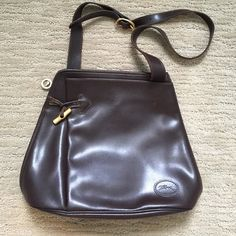 "LONGCHAMP Vintage brown all leather shoulder bag Longchamp Vintage chocolate brown classic leather shoulder bag. Adjustable strap with a 14"" drop. One large zipper with a goldtone toggle that runs from the top & down the side for easy access and too keep your belonging safe. One large fold full leather slip pocket on the front with goldtone bamboo closure. Few minor stains inside as seen in picture two & minor wearing on leather strap by the toggle as seen in picture 3. Two large slip…"