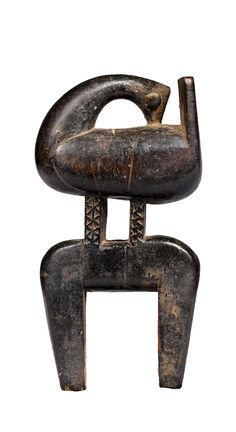 Africa | Heddle pulley from the Kulango people of the Ivory Coast | Wood; aged and used dark brown patina, with light brown on the relief