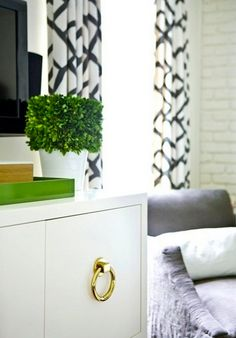 dresser w/ gold hardware, green accents & patterned curtains