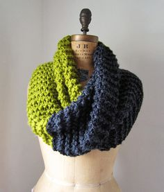 I really like the idea of this two-tone single layer but chunky infinity scarf. I would guess that it is twisted once before the edges are joined together.