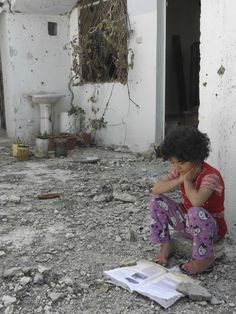 A Syrian girl reads a book in her damaged house in Talbisa area in Homs, northern Syria, April 10, 2012. (REUTERS/Stringer)