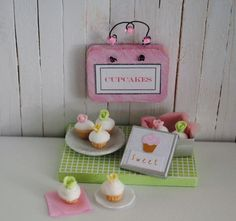Miniature Pink Cupcake Sign, Silver Tin With Cupcakes, And A Plate Of Cupcakes