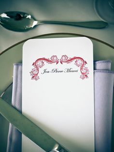 Add a Minimalist Place Card    A detailed red vine at the top of this place card signals a formal dinner is on the way.