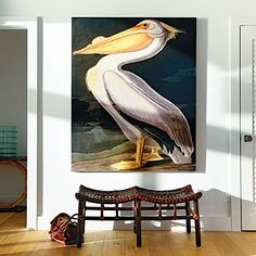 An oversize pelican painting makes for a dramatic focal point in this beachy foyer. Coastalliving.com