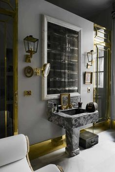 I love the scale of this space, the use of lanterns as sconces, the contrasting trim and the upholstered furniture (barely visible in the corner). Two more features that I love in the bath are the magnifying mirror and a small piece of art.