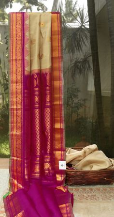This elegant gadwal silk is in a subtle linen tan color and has rudraksh and peacock bhuttas woven all over in gold zari with meenakari highlights. The border and pallu are in magenta shade and hav…