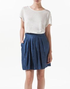 Casual and cool. Love the pleated blue skirt.