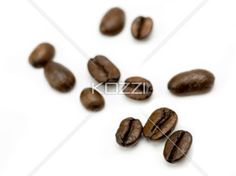 Scattered Coffee Beans - A random arrangement of coffee beans on a white background.