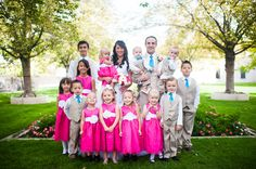 Flower girl + ring bearer outfit ideas - flower girls in bright pink dresses + white sashes + flower accent + ring bearers in tan pants + vest with white button-down shirts + teal neck ties {illuminated Moments}