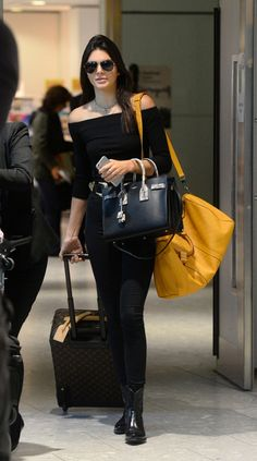 Kendall Jenner is spotted in an off the shoulder black crop top, black tote, yellow duffel bag, high waisted black jeans and patent leather ankle boots.