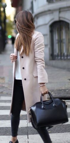 Blush coat over white top and black pants.