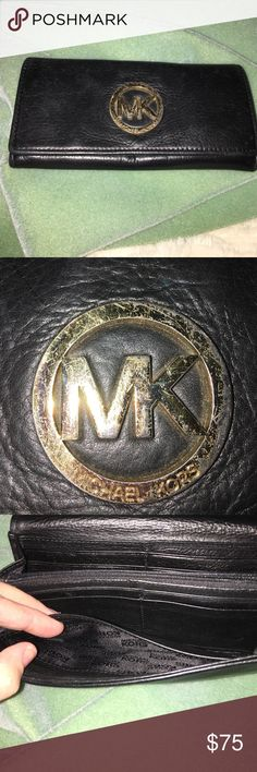 Michael Kors wallet Michael Kors black leather wallet with gold emblem MK on the front. The MK has some scratches on it. Made of soft, supple leather. Very roomy inside. Lots of space for credit cards. Michael Kors Bags Wallets