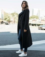 Make a fashion statement in this military maxi coat in navy, the ideal piece to add polish to any ensemble. Crafted from an imported European wool blend, the collared style features a double breasted bodice with crested buttons. Designed to be oversized, this full length military coat is also fully lined. Layer this garment over a  top with jeans and sneakers for a casual daytime look.