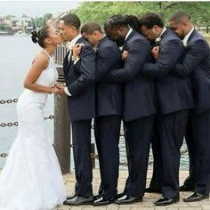 Groomsmen holding up a paralyzed groom so he can kiss his bride