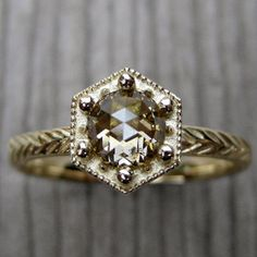 $2,250 BUY NOW This ring is inspired by the vintage settings of the Art Deco period. It's made from recycled gold, and has etched feather details with a champagne diamond on top. The hexagon bezel allows room for bands on either side.