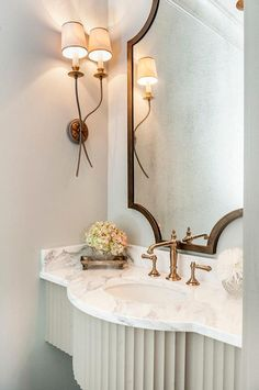 French powder room features a brass vanity mirror over a gray curved floating washstand topped with white marble fitted with oval sink and a brass hook and spout faucet illuminated by brass French sconces.