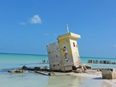 A soft white beach, turquoise waters and a clear blue sky set the perfect balance for a modern architectural ruin.