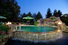 piscine hors sol en pierre, feu dans le jardin, parasols verts, cascades d'eau