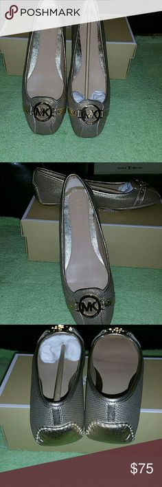 """Cute as ever MK flats just right for any occasion Add some luxury to your look with these shimmery moc flats from MICHAEL Michael Kors.Featured in gold heel Closed round toe Closed back Envelope topline Allover metallic shimmer Metallic faux leather strap on toe with large """"MK"""" logo hardware accent Cushioned footbed Rubber outsole Canvas upper Imported Michael Kors Shoes Sandals"""