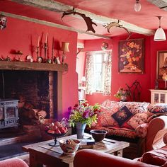 A collection of antique antlers and other quirky vintage pieces catch the eye in this sitting room, with its Madder Red walls by Fired Earth and comfortable sofas piled high with cushions #livingroom #sofa #red