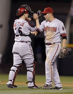 Arizona Diamondbacks catcher Miguel Montero, left, congratulates second baseman Aaron Hill after the Diamondbacks' 8-7 victory over the Colorado Rockies in a baseball game in Denver on Saturday, Sept. 22, 2012. Hill hit a triple to drive in three runs in the sixth inning to lead the Diamondbacks